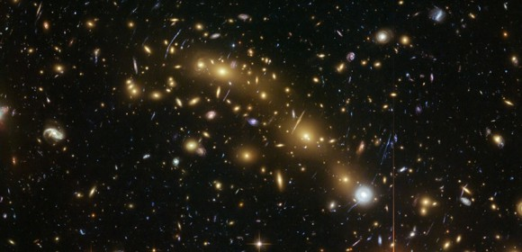 This image from the NASA/ESA Hubble Space Telescope shows the galaxy cluster MCS J0416.1–2403. This is one of six being studied by the Hubble Frontier Fields program. This program seeks to analyze the mass distribution in these huge clusters and to use the gravitational lensing effect of these clusters, to peer even deeper into the distant universe.  A team of researchers used almost 200 images of distant galaxies, whose light has been bent and magnified by this huge cluster, combined with the depth of Hubble data to measure the total mass of this cluster more precisely than ever before. ESA/Hubble, NASA, HST Frontier Fields